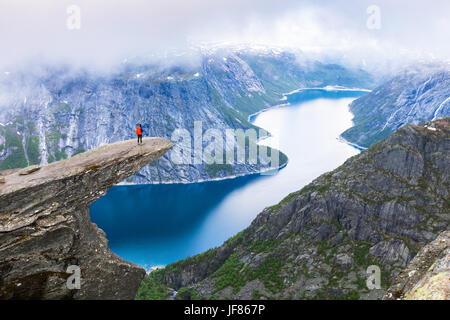 Female hiker debout sur Trolltunga troll (langue) célèbre rocher haut au-dessus d'un lac avec vue panoramique sur Banque D'Images