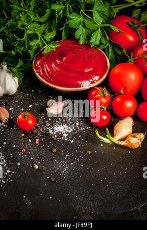 Des tomates biologiques ou sauce ketchup, dans un petit bol. Avec les ingrédients - persil, oignons, ail, tomates, Banque D'Images