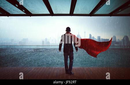 Businessman en costume et cape hero stand à sky garden ,victoire. concept cityscape background , jour de pluie. Banque D'Images