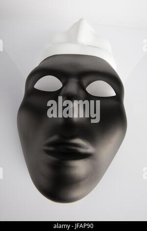Les masques noirs et blancs réunis sur fond réfléchissant blanc. Verticale de l'image, grand angle, vue du dessus. Banque D'Images