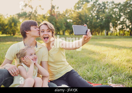 Happy smiling family photographié dans le parc. Banque D'Images