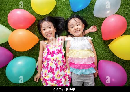 Peu de filles asiatiques chinois couché dans l'herbe parmi les ballons colorés à l'extérieur parc Banque D'Images