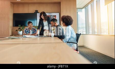 Groupe ethnique de plusieurs jeunes gens d'affaires réunion dans la salle de conférence. Les professionnels de la Banque D'Images