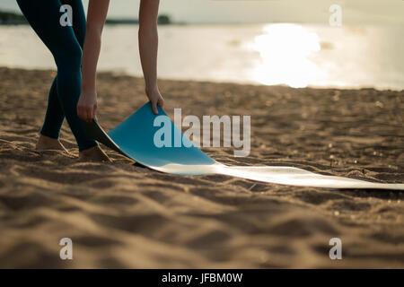 Attractive young woman folding yoga vert tapis de sol fitness ou après l'entraînement à la plage.
