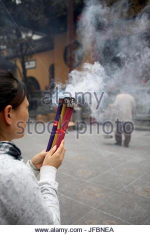 Une femme prie en brûlant une offrande de l'encens au Temple du Bouddha de Jade. Banque D'Images