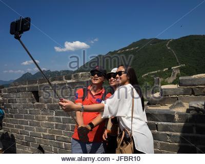 Les adolescents tourner un à selfies la Grande Muraille de Chine, à l'aide d'un téléphone cellulaire. Banque D'Images