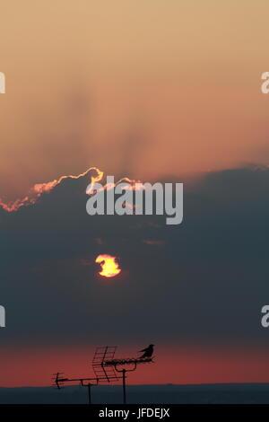 Coucher du soleil à travers les nuages Banque D'Images