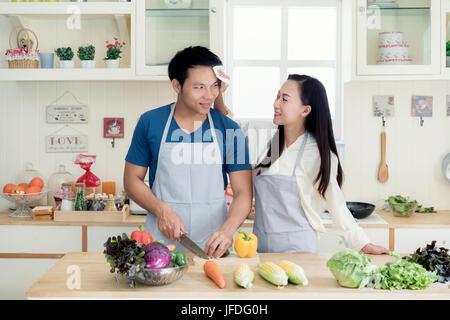 Belle jeune femme asiatique aidant à sec mari sueur sur son visage dans la cuisine à la maison. Heureux couple love concept.