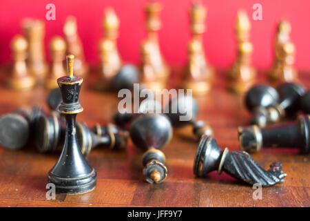 Pièces des échecs en bois ancienne sur un ancien échiquier. Sur un fond rouge.