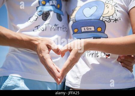 Couple smiling et embrassant près de l'arche de mariage sur la plage. Miel, sur mer ou océan. Banque D'Images