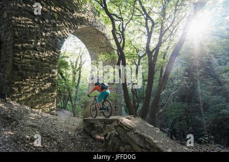 Man riding bike sur sentier par des mur de pierre en forêt