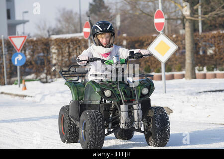 Girl riding quad sur route couverte de neige Banque D'Images