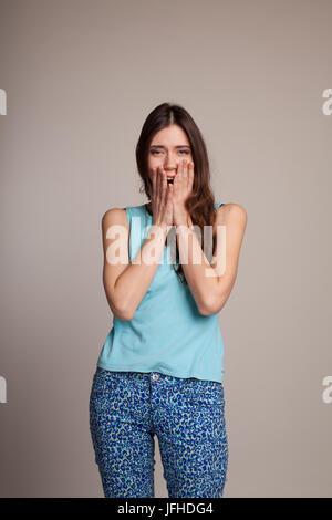 Jolie fille surpris couvrant sa bouche Banque D'Images