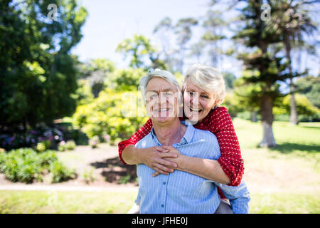 Happy senior man giving a piggy back to senior woman Banque D'Images