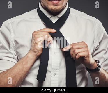 Libre d'un jeune homme dans une chemise debout dans un studio sur un arrière-plan gris lier sa cravate Banque D'Images