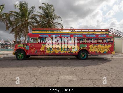 Un vieux bus scolaire jaune d'Amérique du Nord peints en rouge vif pour prendre les touristes à Aruba sur un bus parti Kukoo Kitchen Kunuku
