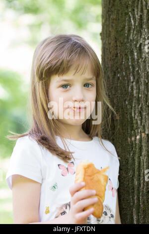 Jolie petite fille aux grands yeux bleus aime manger son croissant préférés