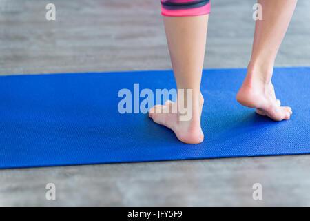 Jeune femme debout sur le yoga ou bleu mat. de remise en forme de l'exercice, en bonne santé, garder l'ajustement Banque D'Images