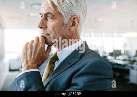 Vue de côté tourné de mature businessman thinking with hand on chin. Gros plan du young entrepreneur looking pensive Banque D'Images