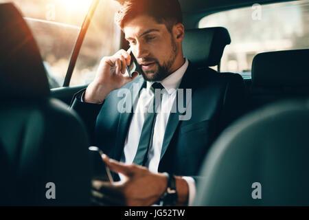 Young businessman talking on mobile phone and using tablet pc tout en étant assis sur le siège arrière d'une voiture. Homme de race blanche d'affaires voyageant par un t