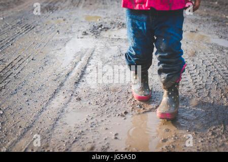 Un enfant marche dans la boue le long d'une route de campagne en Pennsylvanie. Banque D'Images