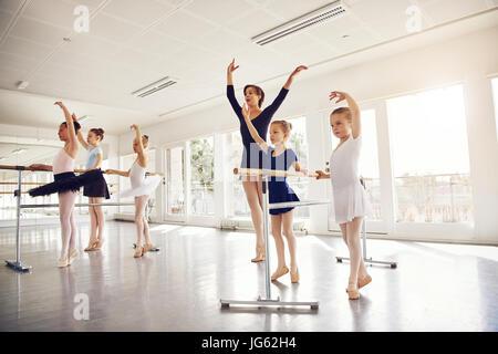 Les jeunes filles et femmes teacher standing with hands up pendant l'exécution de ballet dans la classe. Banque D'Images