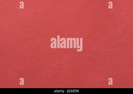 Mur en stuc peint rouge. texture de fond. Banque D'Images