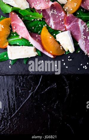 Salade avec du jambon jamon serrano, camembert, melon, roquette sur la plaque d'ardoise noire sur fond noir. Vue Banque D'Images