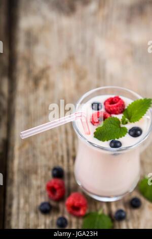 Les smoothies ou yaourt avec les baies fraîches sur une table en bois. milkshakes avec framboises, myrtilles, abricots Banque D'Images