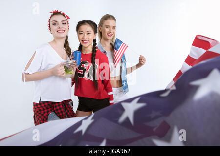 Les jeunes femmes avec le drapeau américain à la caméra et à boire des boissons, Independence Day Celebration
