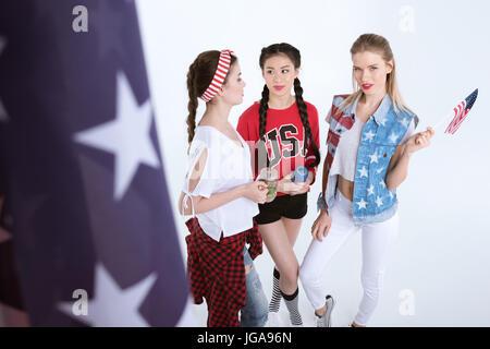 Smiling girls avec le drapeau américain à parler et boire des boissons isolé sur blanc, Independence Day Celebration