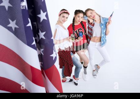 Les jeunes femmes avec le drapeau américain de boire des boissons isolé sur blanc, Independence Day Celebration