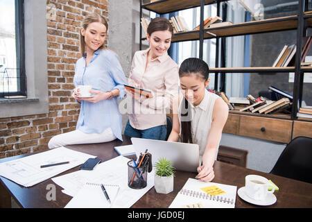 Affaires multiculturelles travaillant avec ordinateur portable et tablette numérique sur le lieu de travail dans Banque D'Images