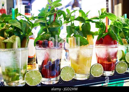 Des cocktails de fruits et de petits fruits à la menthe sur le comptoir d'un café