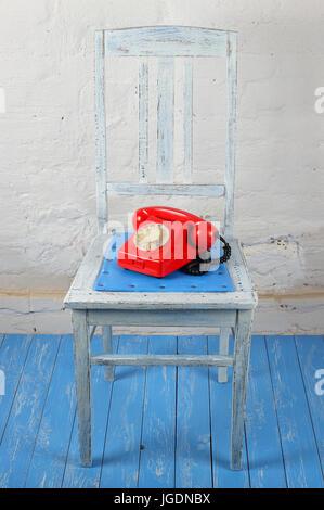 Style rétro vintage Rouge - téléphone portable, sur une vieille chaise bleu en bois blanc et un fond en briques. Banque D'Images