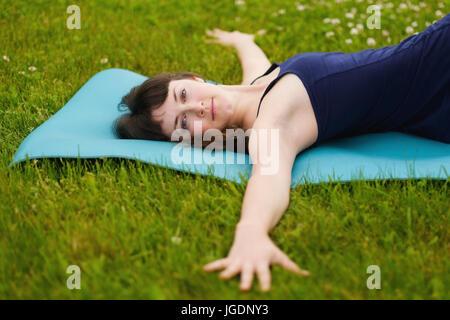 Belle jeune femme caucaisan hors travail à l'extérieur sur le tapis bleu. Jathara Parivartanasana vue supérieure Banque D'Images
