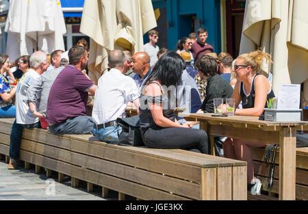 Les gens assis dehors sur des tables en bois et bancs pour un café et un bar sur une chaude journée d'été. Banque D'Images