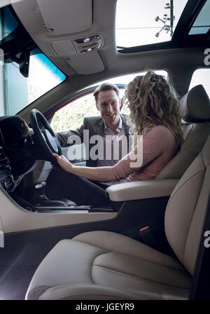 Smiling salesman talking to female customer sitting in car Banque D'Images