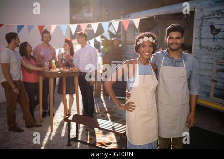 Portrait of happy waiter waitress standing et avec les clients en arrière-plan Banque D'Images