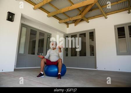Senior man exercising with dumbbells sur boule d'exercice dans le porche Banque D'Images