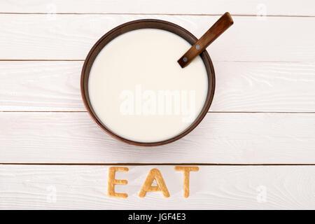 Vue rapprochée du lait et la cuillère dans un bol et manger des céréales à déjeuner de mot Les lettres sur le dessus Banque D'Images