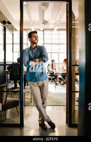 Full Length portrait of happy young man standing in office avec les bras croisés et à la voiture. Au bureau exécutif Banque D'Images