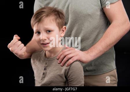 Cropped shot du père menaçant et gesticulant de peur petit fils, les problèmes de famille concept Banque D'Images