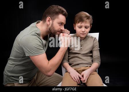 Père en colère menaçante et gesticulant de peur petit fils assis sur une chaise, les problèmes de famille concept Banque D'Images