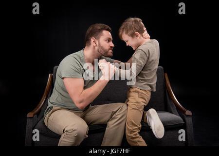 Père en colère menace de peur petit garçon isolé sur noir, problèmes de famille concept Banque D'Images