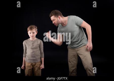 Père en colère menaçante et gesticulant de peur petit fils, les problèmes de famille concept Banque D'Images