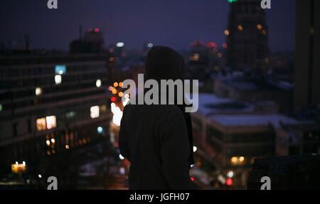 Silhouette of man sur le toit en ville la nuit Banque D'Images
