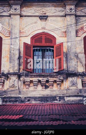 Des détails architecturaux de type colonial montrant une fenêtre aux volets en bois. Hoi An, Vietnam central. Banque D'Images