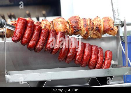 Et saucisses chorizo poulet rôti sur un charbon Spit barbecues torréfacteur Banque D'Images