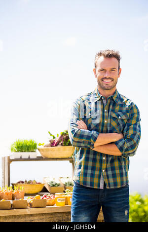Portrait of young man with arms crossed standing at farm Banque D'Images